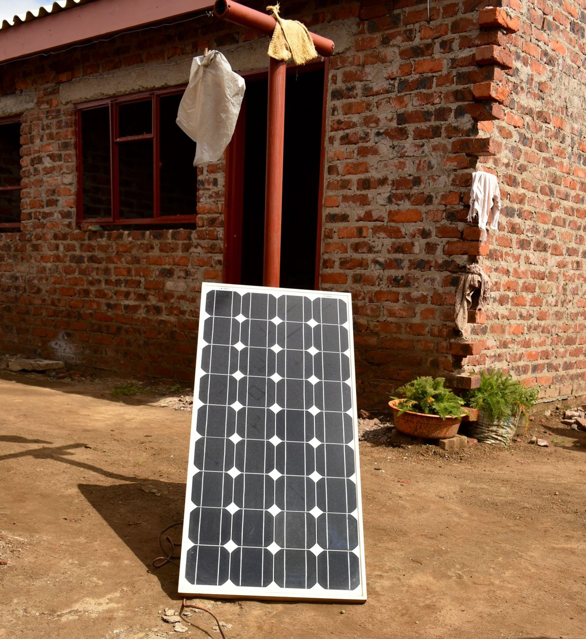 """A full-sized """"roof"""" solar panel leaning up against a clothesline. Often roof-mounting panels is structurally challenging, so it is not uncommon to see these larger panels placed nearby on the ground."""