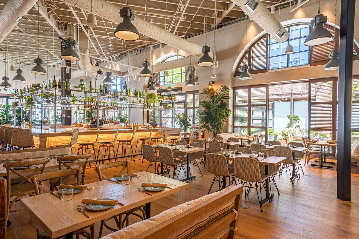 A new restaurant shows off an indoor-outdoor space, bar, tables, and booth seating.