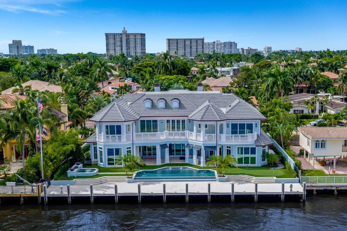 Aerial backyard shot of a waterfront home with a grey roof, white walls and pool and jacuzzi out back