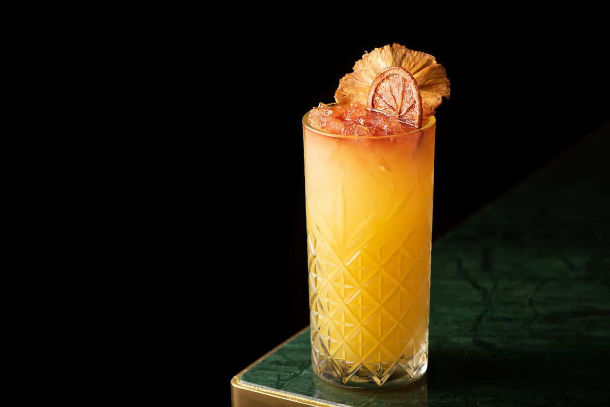 A golden cocktail with dried fruit garnish.