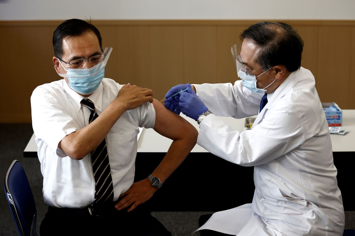 On the left, Dr. Kazuhiro, the Director of Tokyo Medical Center is sitting down, wearing a mask, with his right sleeve rolled up. A doctor is sitting next to him, wearing a mask and gloves, and is giving him Japan's first dose of the coronavirus vaccine through injection.