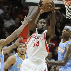Houston Rockets' Patrick Patterson (54) grabs a rebound while surrounded by Denver Nuggets' Arron Afflalo (6), JaVale McGee, center, and Al Harrington, right, in the first half of an NBA basketball game Monday, April 16, 2012, in Houston.