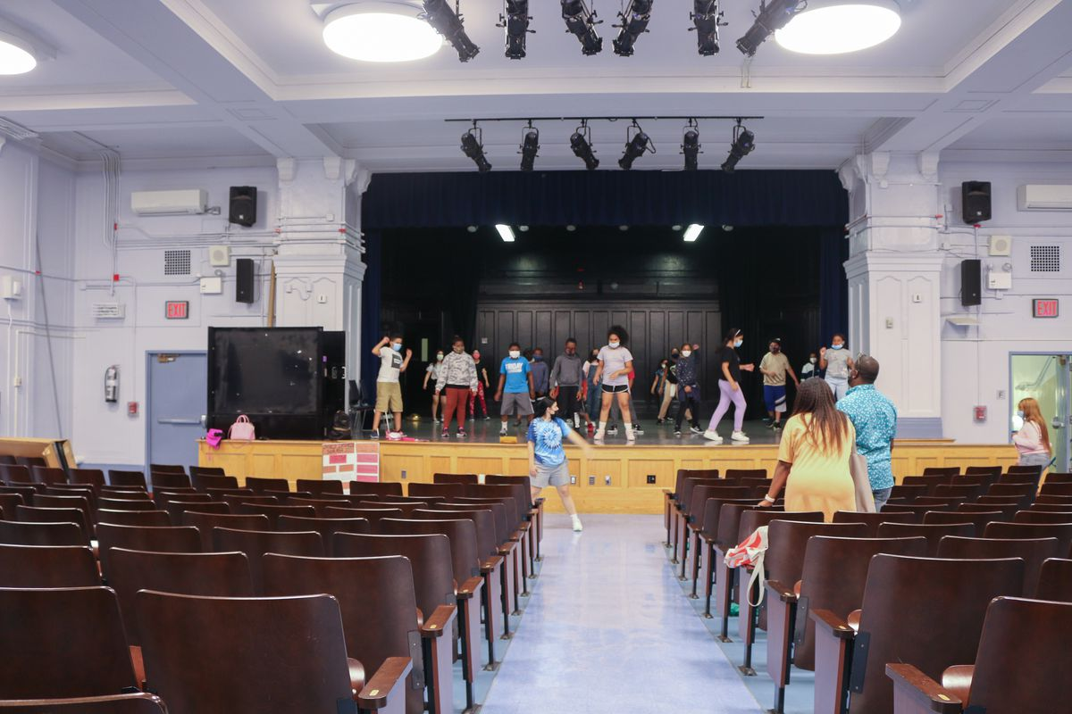 Students stand on a stage in an auditorium.