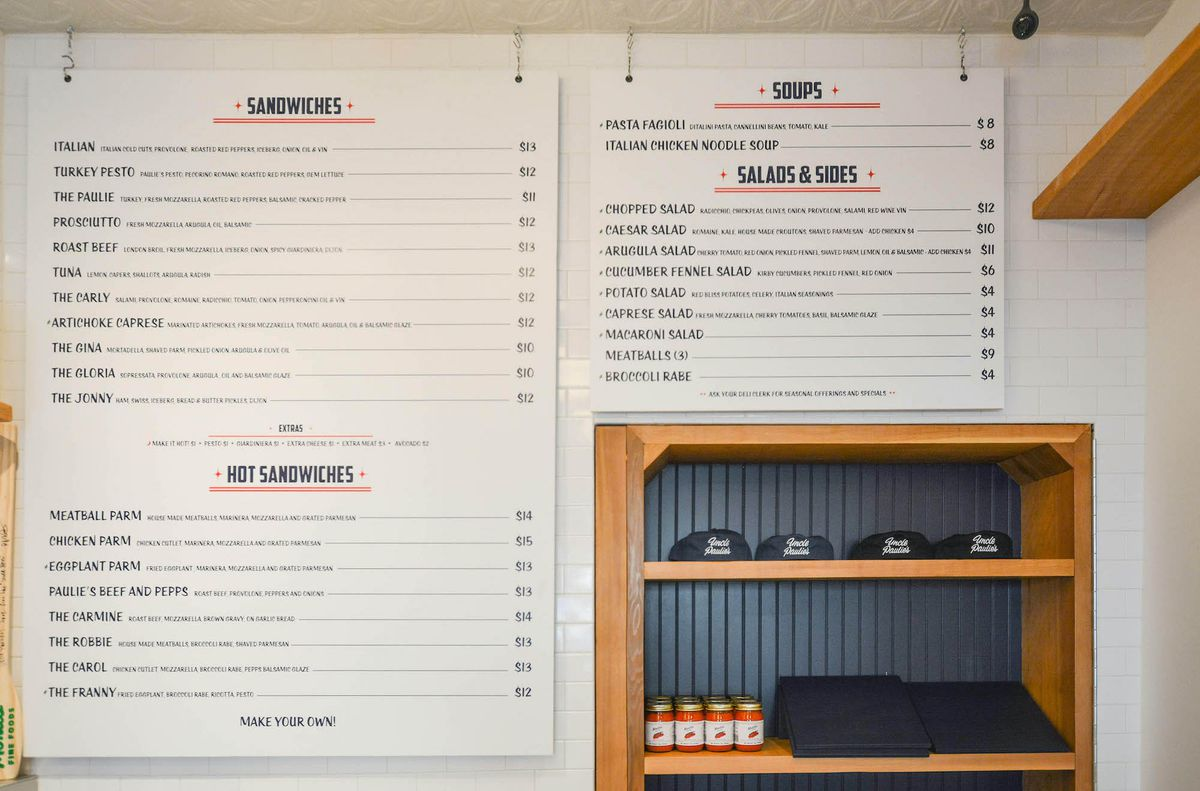 A menu board hangs, showing Italian deli sandwiches.