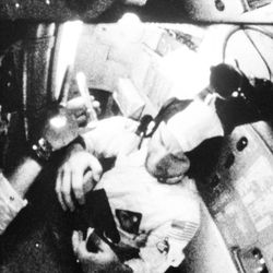 Capt. James A. Lovell Jr., Apollo 8 command module pilot, examines a package in his lap as another crew members holds a flashlight to aid in the inspection, Dec. 30, 1968.