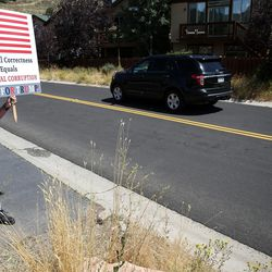 Dave Novak, a Park City resident and Donald Trump supporter, holds a sign as former President Bill Clinton's motorcade arrives for a fundraiser for his wife, Democratic presidential nominee Hillary Clinton, in the Glenwild community of Park City on Thursday, Aug. 11, 2016.