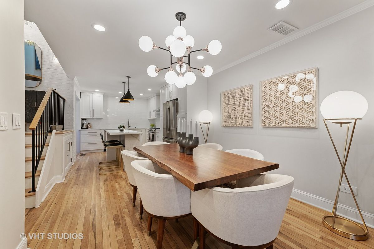 A dining room with an open kitchen. There is a wood table with a modern candelabra, gold and glass shade light fixture, fiber wall art. and the kitchen in the distance.