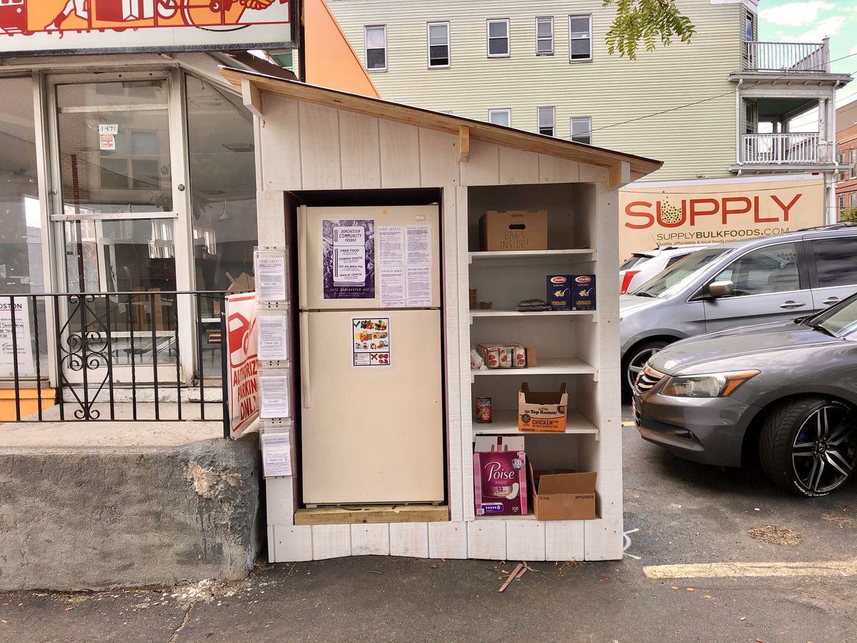 A fridge and shelves sit under a slanted roof in a parking lot. The shelves are stocked with various pantry staples.