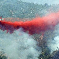 An air tanker drops retardant on the Mill Flat fire in New Harmony on Sunday. Eleven structures burned over the weekend, but no injuries have been reported.