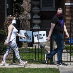 People wearing face masks walk by signs of encouragement outside a home in the 2600 block of West Wilson Avenue in the Lincoln Square neighborhood, Tuesday, April 7, 2020.