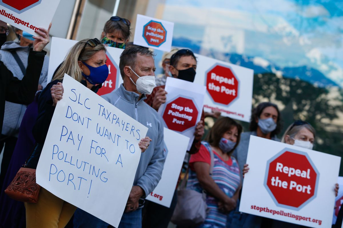 Members of Stop the Polluting Port Coalition holds signs outside the offices of the Utah Inland Port Authority in Salt Lake City on Monday, Sept. 20, 2021, protesting the port authority's planned vote to adopt a public infrastructure district.
