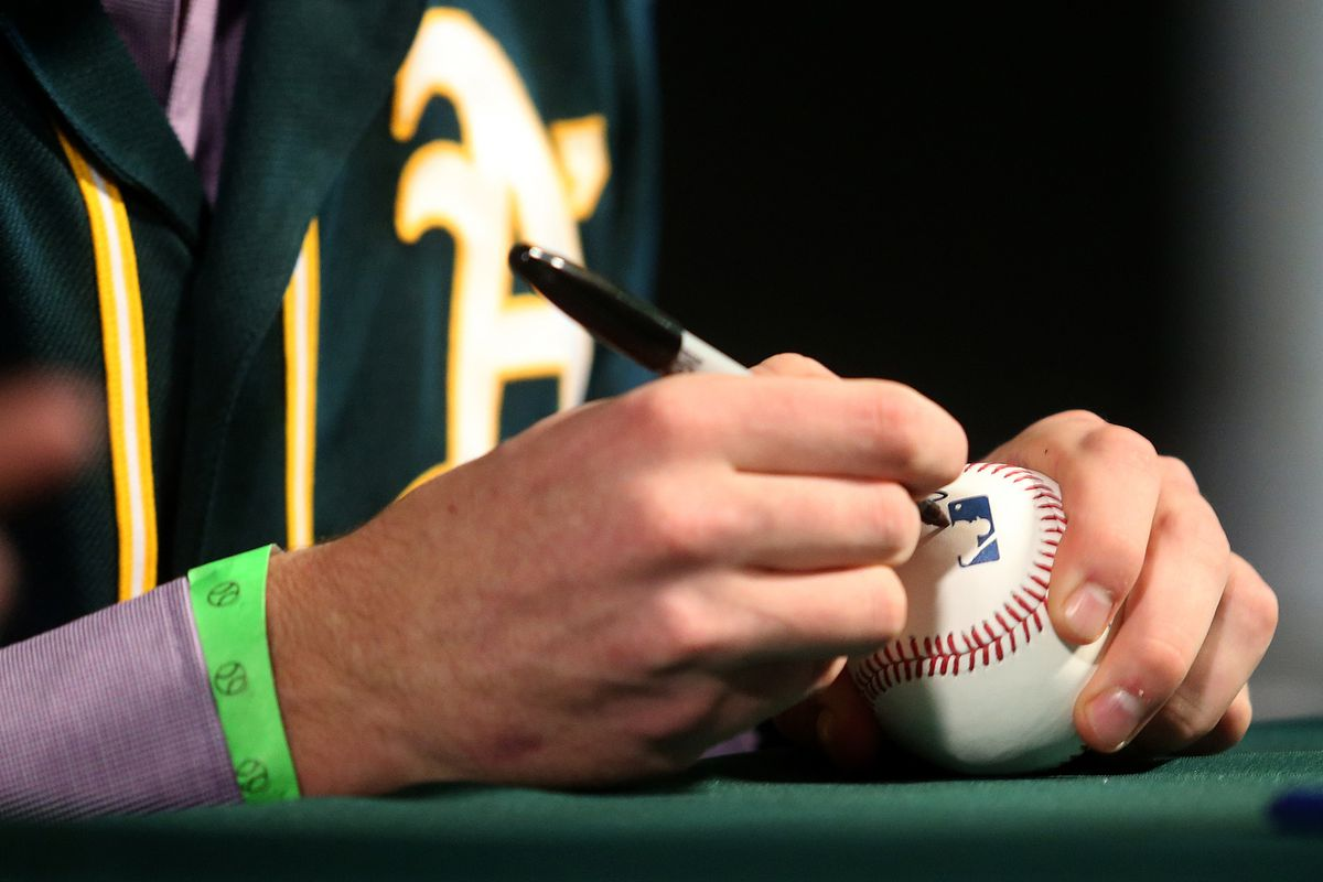Oakland Athletics pitcher Chris Bassitt signs a basebll at Fan Fest on Sunday, Feb. 8, 2015, in Oakland, Calif. (Aric Crabb/Bay Area News Group)