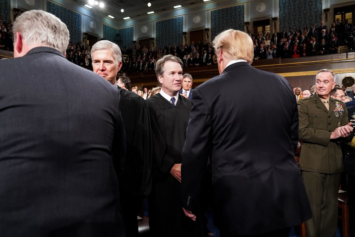 Brett Kavanaugh, facing the camera, shakes hands with Donald Trump, seen from the back.