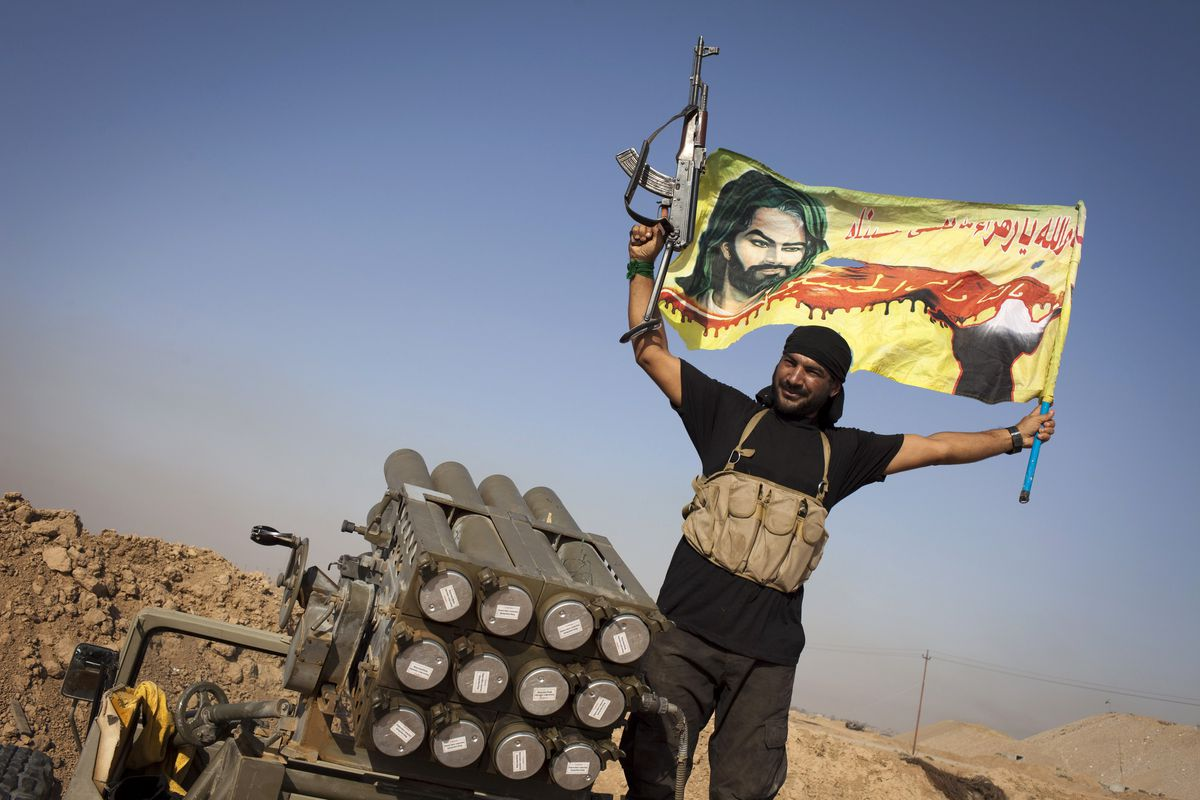 An Iraqi militia fighter from Shia cleric militia waves a flag next to a rocket launcher during heavy clashes with Islamic State in Iraq and Syria (IS) fighters.