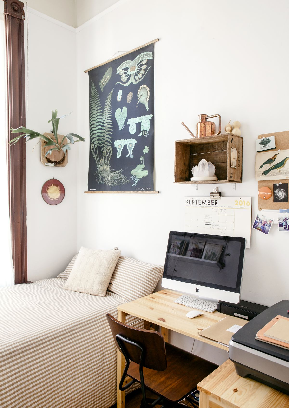 A bedroom with a bed that has patterned bed linens, a wooden desk, multiple works of art on the walls, and a plant.