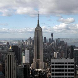 This April 27, 2012, photo shows the Empire State Building, center, and One World Trade Center, rear right, in New York. One World Trade Center, the giant monolith being built to replace the twin towers destroyed in the Sept. 11 attacks, will lay claim to the title of New York City's tallest skyscraper on Monday, April 30, as workers erect steel columns that will make its unfinished skeleton a little over 1,250 feet, just high enough to peak over the observation deck on the Empire State Building.