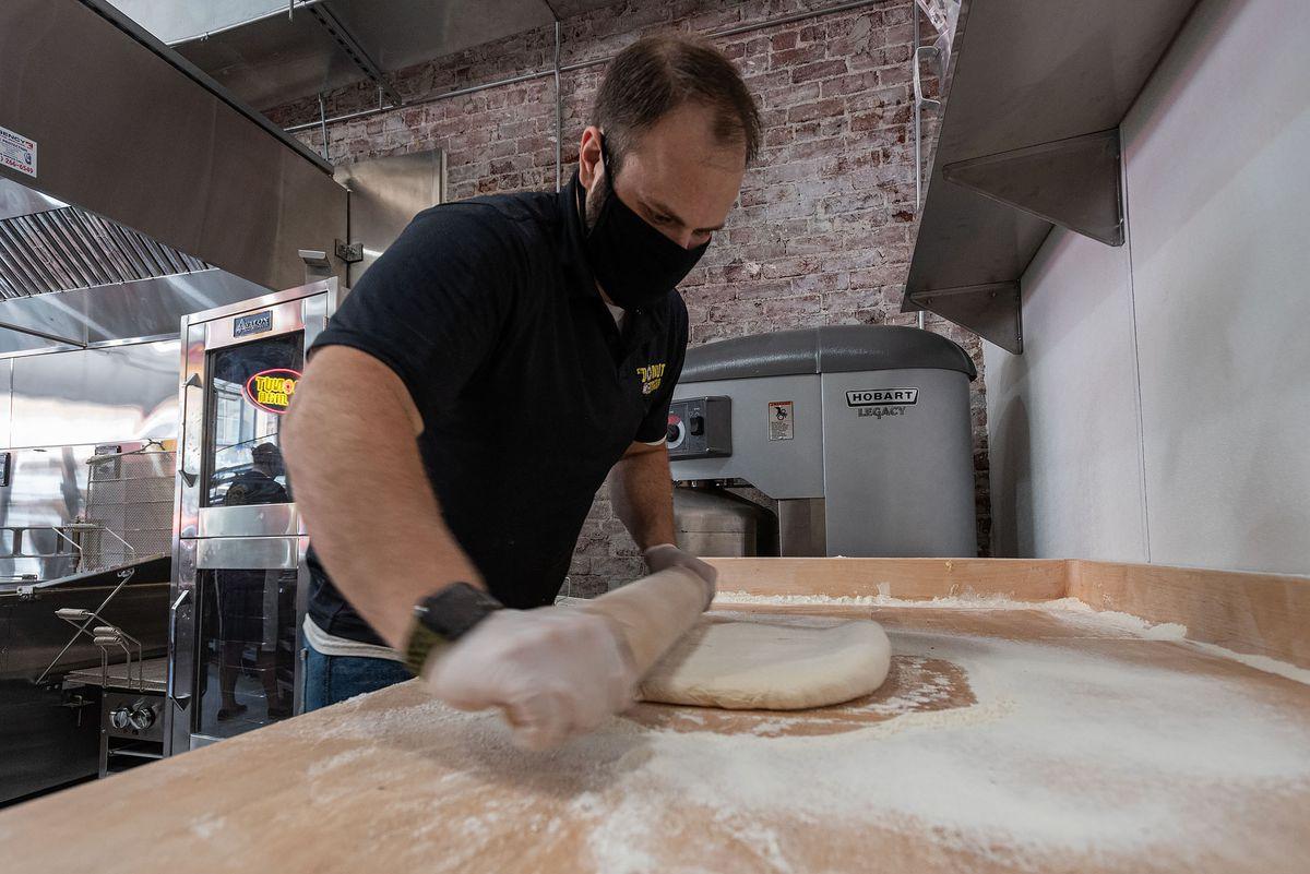 A doughnut shop worker in a mask rolls out dough.