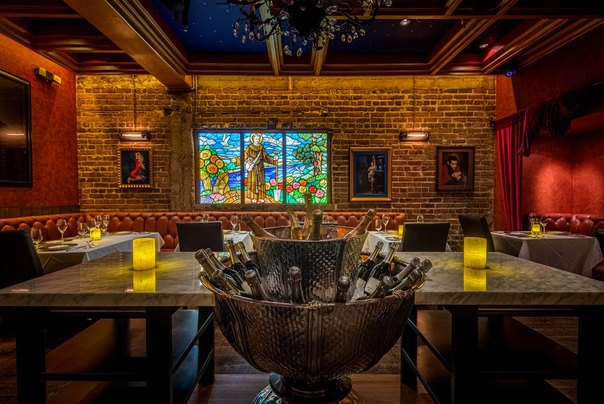 Exposed brick, vintage artwork, stained glass and wine bottle holder in a dimly lit steakhouse dining room.