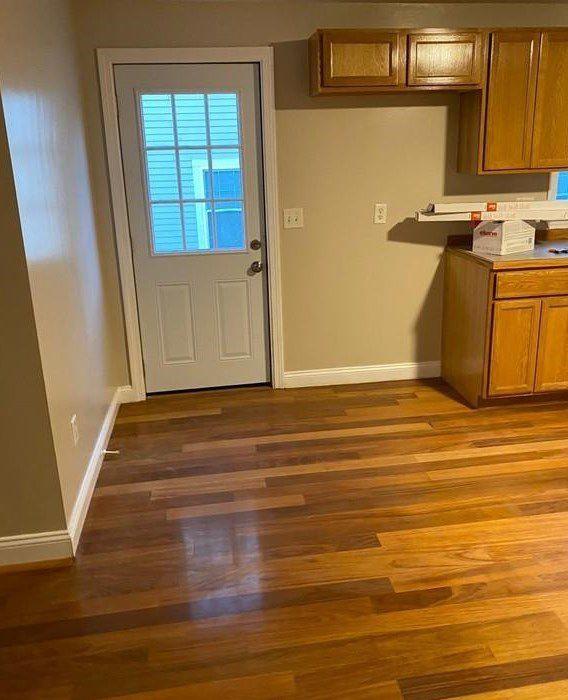 An apartment door next to a kitchen counter.