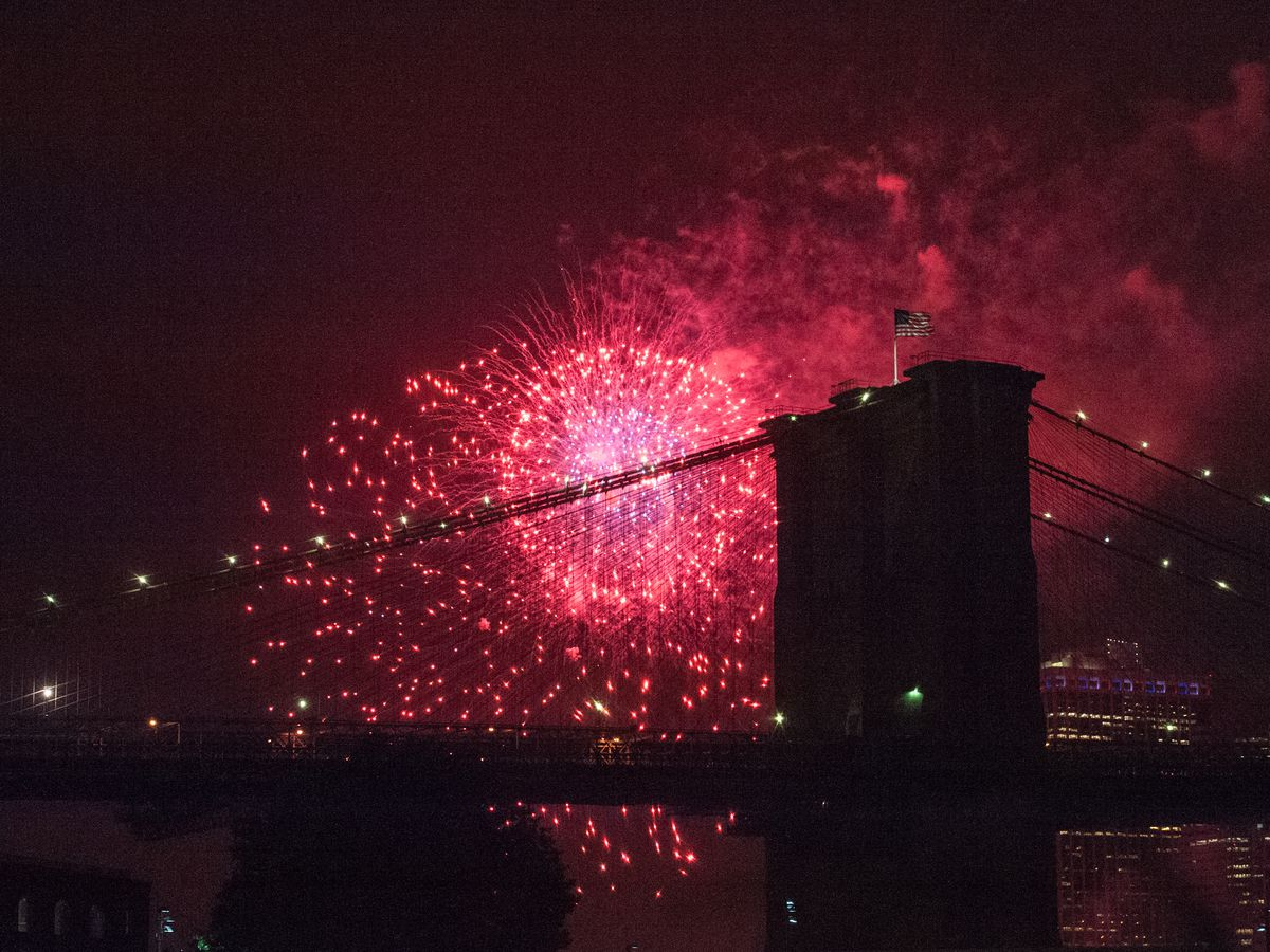 Red fireworks over a silhouetted bridge at night.