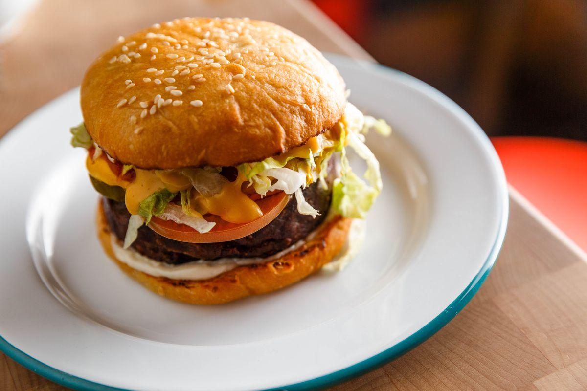 The vegan cheeseburger at Lekka Burger sits on a white plate with a blue rim