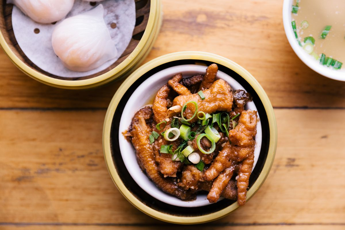 Two prawn dumplings, a small bowl of braised chicken feet with scallions on top, both served in mini steamers.