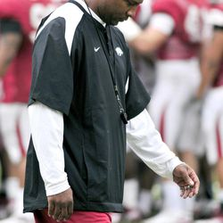 CORRECTS TO ARKANSAS DEFENSIVE COORDINATOR PAUL HAYNES, NOT ARKANSAS INTERIM HEAD COACH TAVER JOHNSON - Arkansas defensive coordinator Paul Haynes walks by as the team huddles before NCAA college football practice in Fayetteville, Ark., Friday, April 13, 2012.