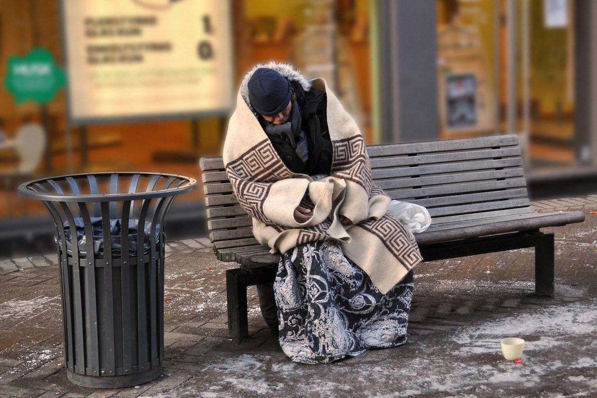 A homeless person sits on a bench.