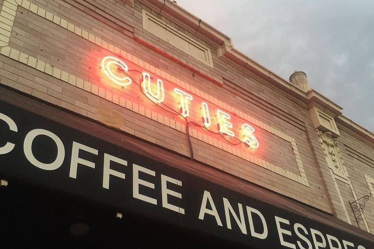 Cuties Coffee neon sign hangs on a brick building over a coffee shop.