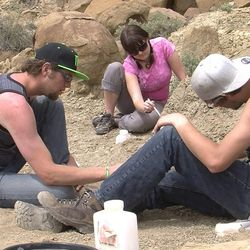 Snow College students Jason Dillingham, left, and Alli Lancaster with an unidentified student work at a dig at the Grand Staircase-Escalante National Monument on April 4, 2014.