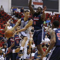Utah Jazz's Jared Cunningham passes around Washington Wizards' Damion James during the first half of their NBA summer league basketball game Wednesday, July 15, 2015, in Las Vegas. (AP Photo/John Locher)