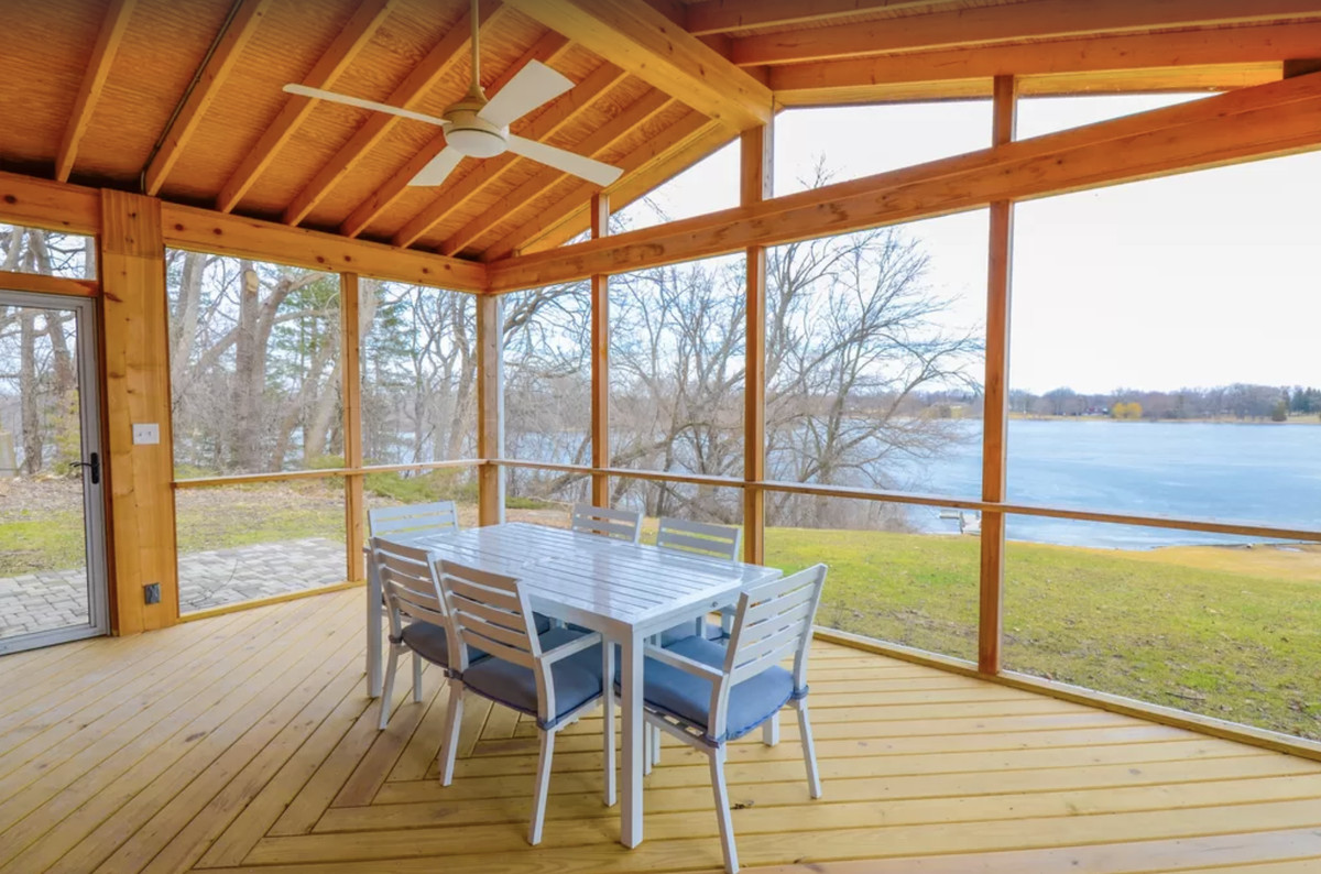 An enclosed patio with a table, large deck, and beautiful views of a private lakefront.