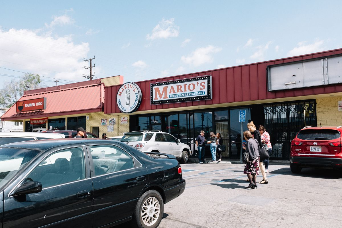 People young and old file into Mario's Peruvian Restaurant in a small strip mall. The buildings are clad in yellow brick. Next-door is Ramen Koo.