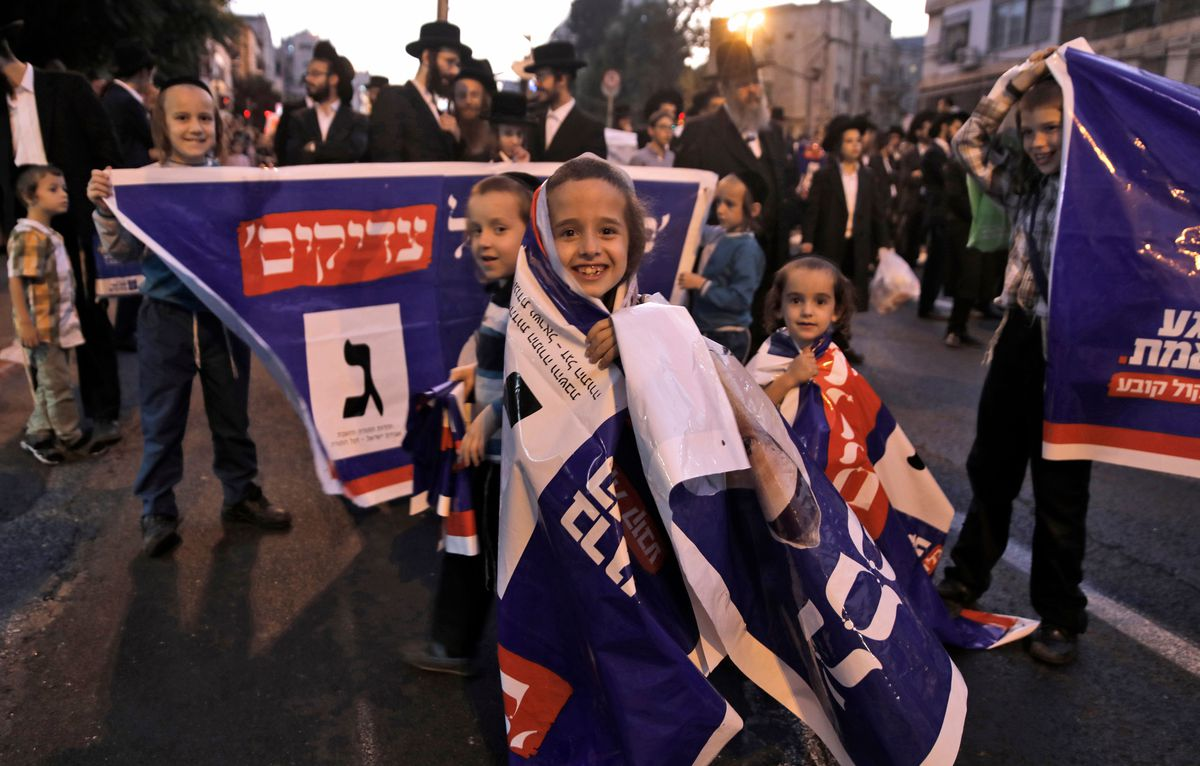 Israeli younger folk wrap themselves in rally banners at a 2019 election rally.