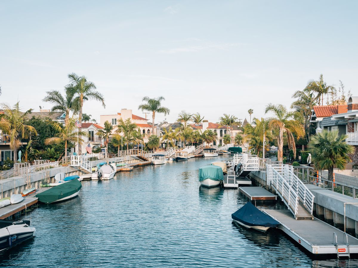 A body of water surrounded by palm trees and houses. There are kayaks and boats sitting along docks on the water.
