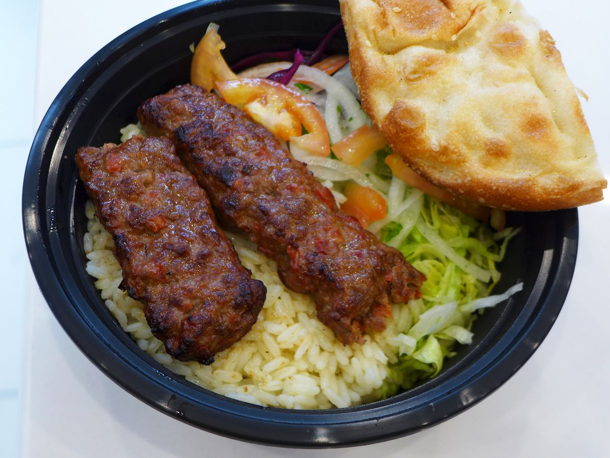A ground lamb kebab broken in half and cradled in off-white somewhat greasy rice.