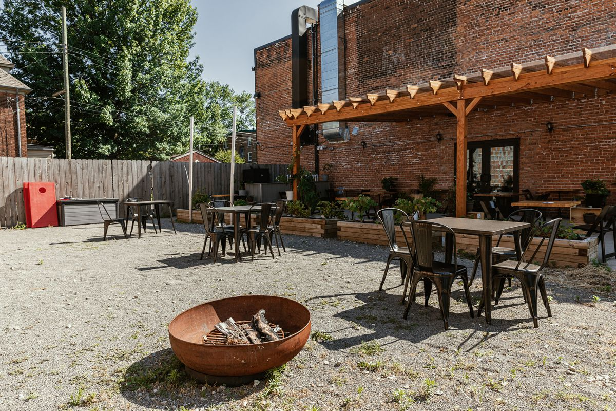 A fire pit in the foreground with socially distanced tables and a pergola in the background.