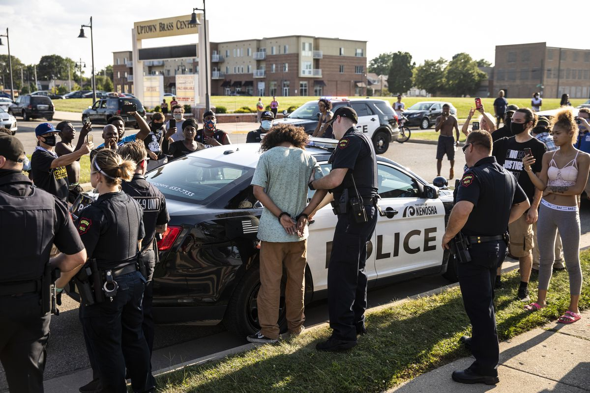 Kenosha police take a man into custody as members of the community watch Thursday night, the fifth night of unrest after police shot Jacob Blake.