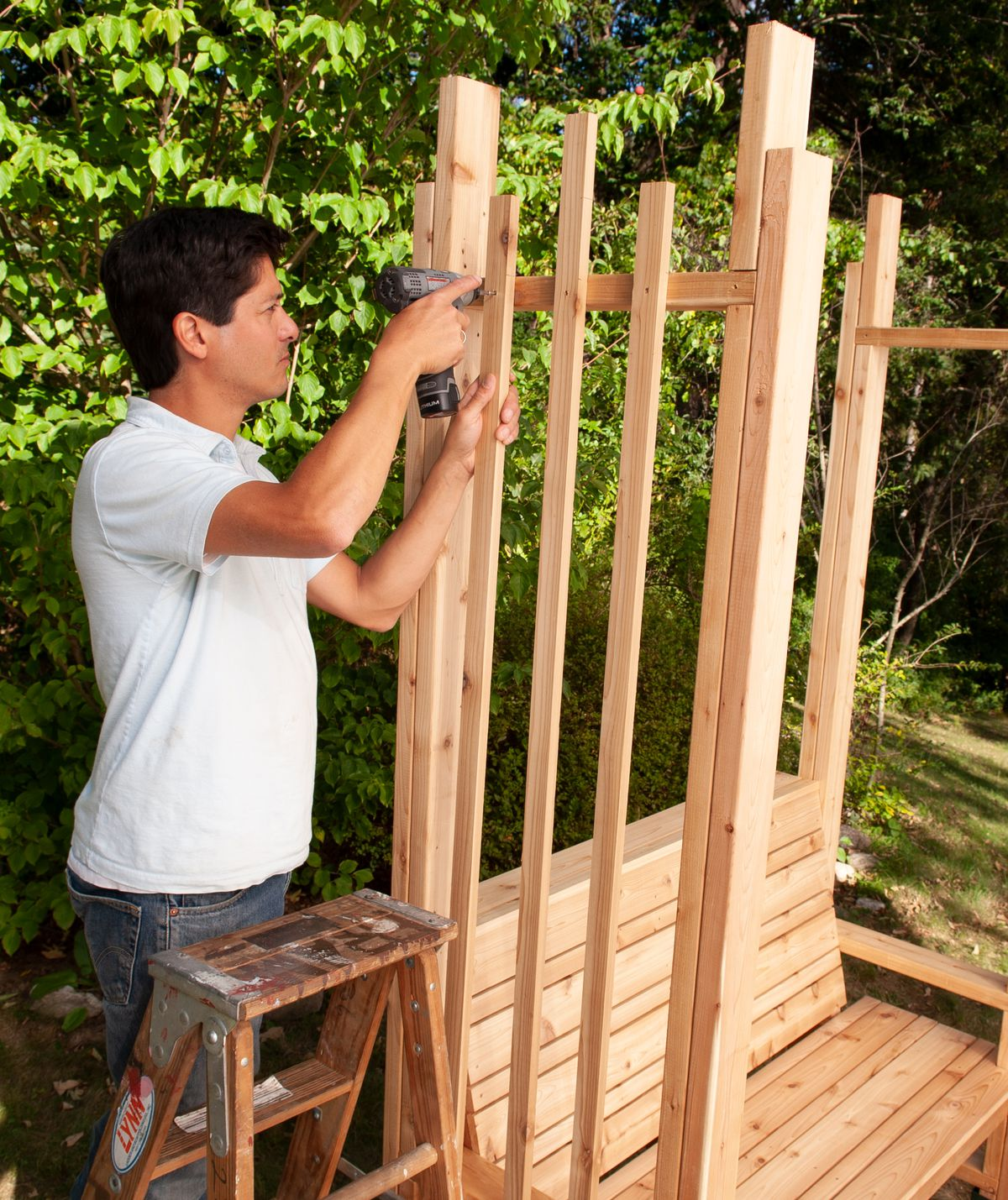 Man Installs Remaining Crosspieces And Vertical Strips Of Arbor Bench