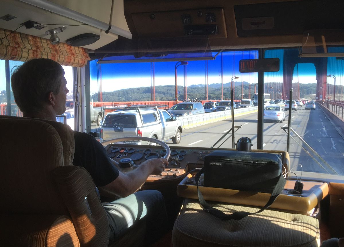 Man in '70s RV driving on Golden Gate bridge as confused motorists look on.
