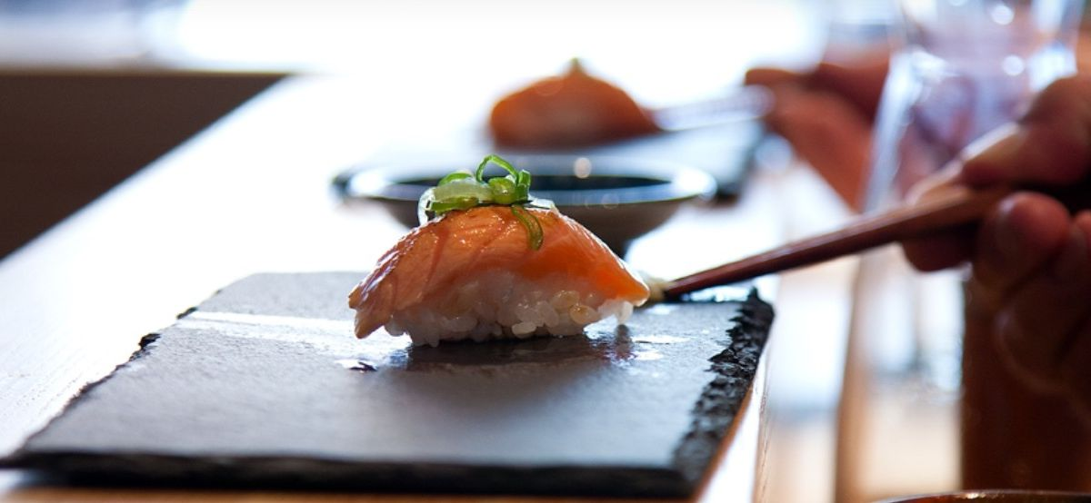 A single piece of sushi, topped with a small dollop of greens, sits on a slate board with chopsticks resting nearby