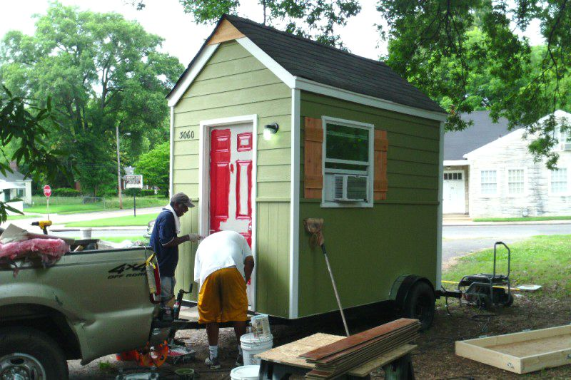 A tiny green house with a red door. There are two people in front of the door. The roof is dark grey and sloped.