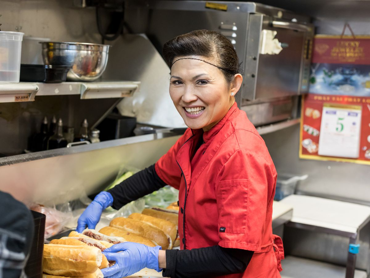 A smiling woman in a red shirt and hair net in the kitchen at Quang, building banh mi