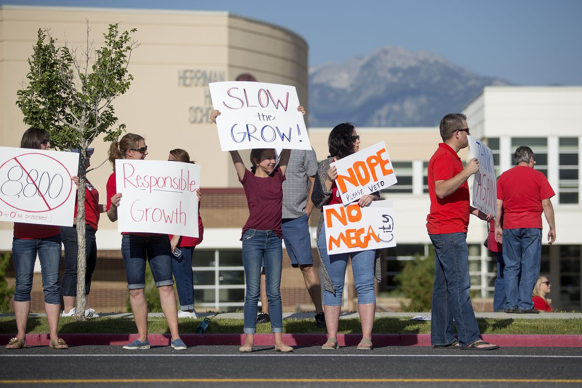 Protestors hold signs opposing the Olympia Hills development proposal before a town hall meeting in Herriman High School on Thursday, June 14, 2018. Many members of the community voiced concern about the high density of the development, which would suppor