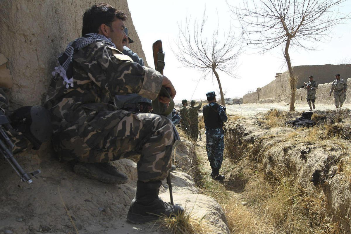 Afghan security forces take position behind a wall after Taliban militants opened fire on a delegation of senior Afghan officials in Panjwai, Kandahar province south of Kabul, Afghanistan, Tuesday, March. 13, 2012.