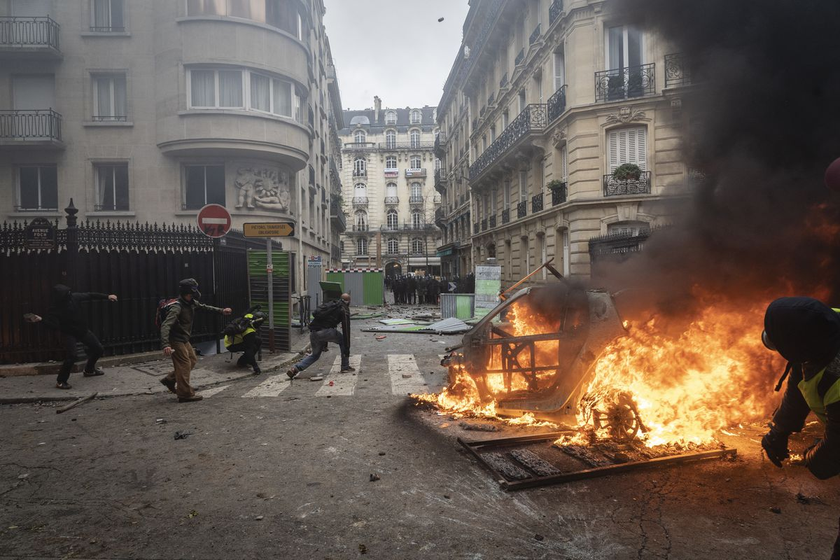 Fires burn as demonstrators collide with the riot police during the demonstration
