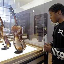 In a Monday, April 9, 2012 photo, Lorryan Smith, 12, looks at violins on display at the Violins of Hope exhibit at UNC Charlotte in Charlotte, N.C. Eighteen violins recovered from the Holocaust and restored by  Israeli violin maker Amnon Weinsten make their U.S. debut on Sunday, April 15. Some were played by Jewish prisoners in Nazi concentration camps, while others belonged to the Jewish Klezmer musical culture. (AP Photo/Chuck Burton)