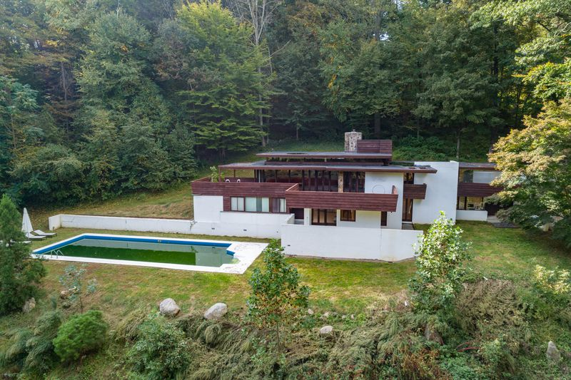 A midcentury modern house in white with dark brown trim. The house is surrounded by greenery and has a pool.