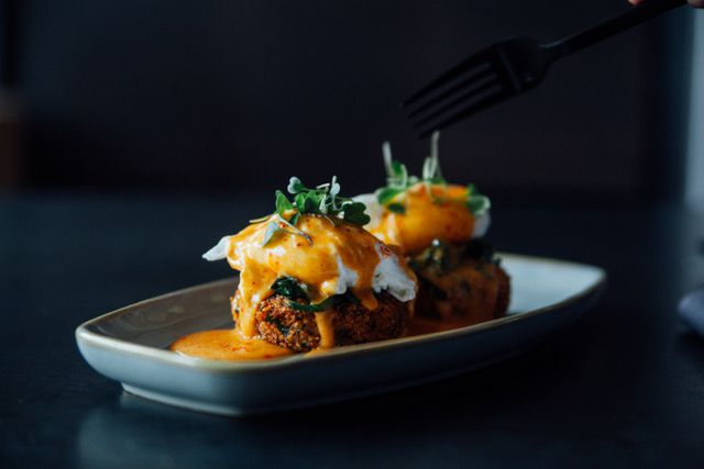Two croquettes topped with poached eggs and an orange sauce on a gray, rectangular plate.