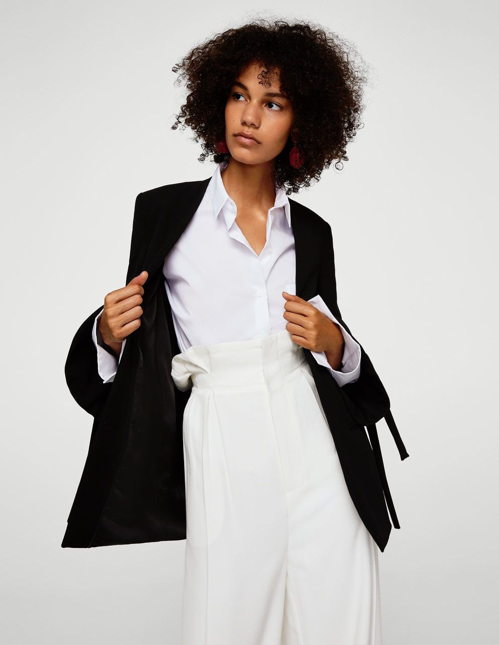 91fd66e31ead3 A model wearing a blouse, blazer, and white trousers
